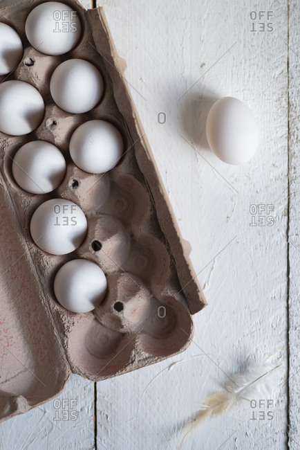 White eggs in a eggs box on a white wooden background with negative space