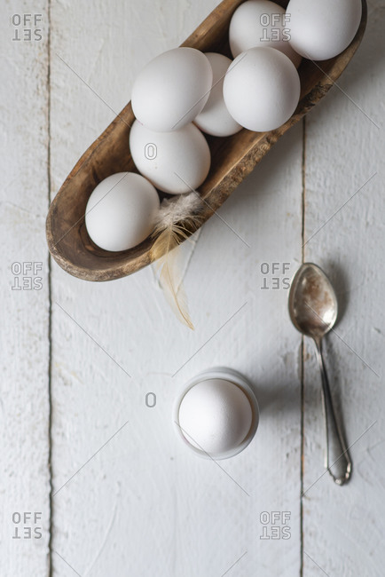 A cooked egg as breakfast on a white wooden background