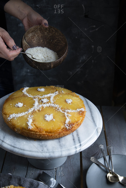 Hans decorating an upside down pineapple cake with coconut rasps