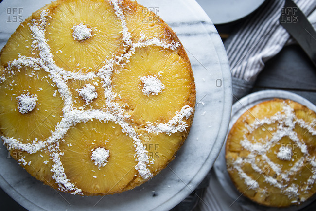 Overhead view of an upside down pineapple cakes decorated with coconut rasps on a marble cake stand