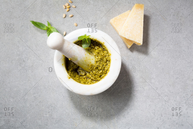 Overhead view of green pesto in white mortar and cheese