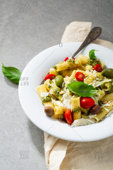 Pasta with basil pesto and cheese on white plate