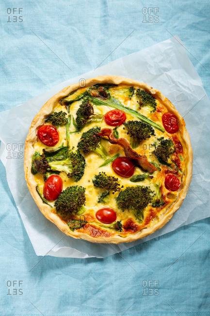 Broccoli quiche on blue linen surface