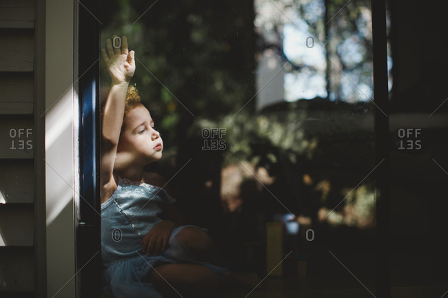 Portrait of  a little girl wearing ballerina outfit  looking out of window