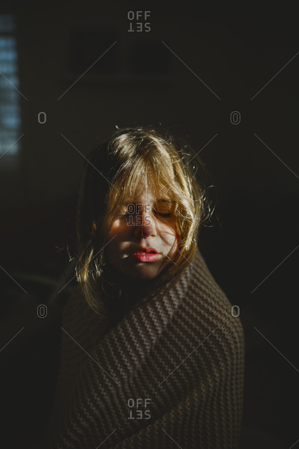 A girl wrapped with a blanket closing her eyes to window light
