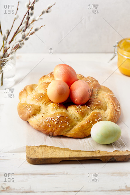 Traditional easter bread - braided pastry with sesame seeds decorated with pink festive eggs