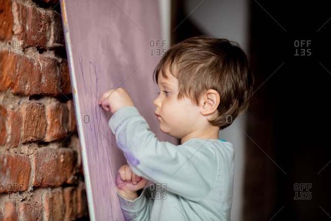 Cute toddler boy drawing on a panel at home. Side view