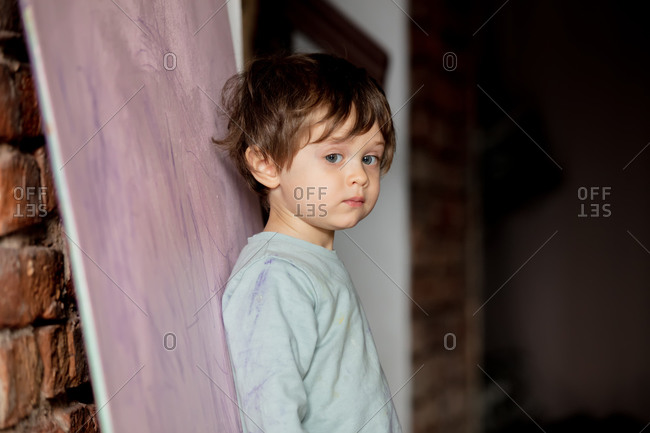 Little toddler boy stay next to the drawings