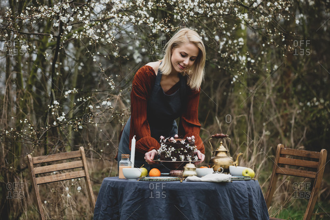 Woman in an apron sets the table for tea in the garden near the cherries garden