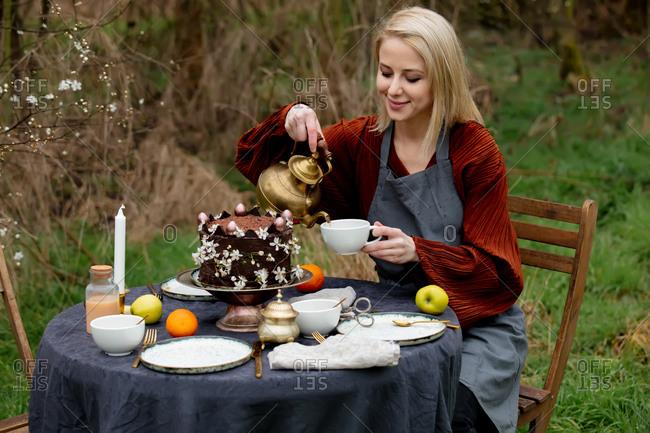 Woman pours tea into a cup in the garden near the cherries garden