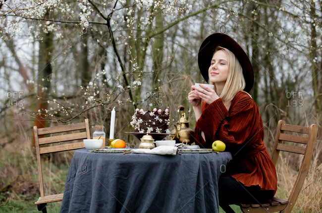 Beautiful woman drinking a tea in a garden