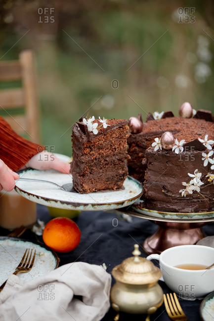 Woman eating a chocolate cake in a garden