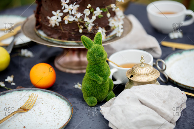 Easter rabbit, teapot, cake and cups ready for tea time in the garden in spring among the flowering trees