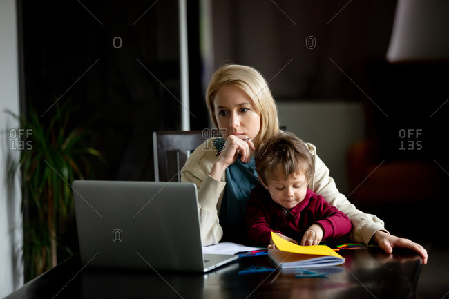 Young mother works at a computer at home with her child