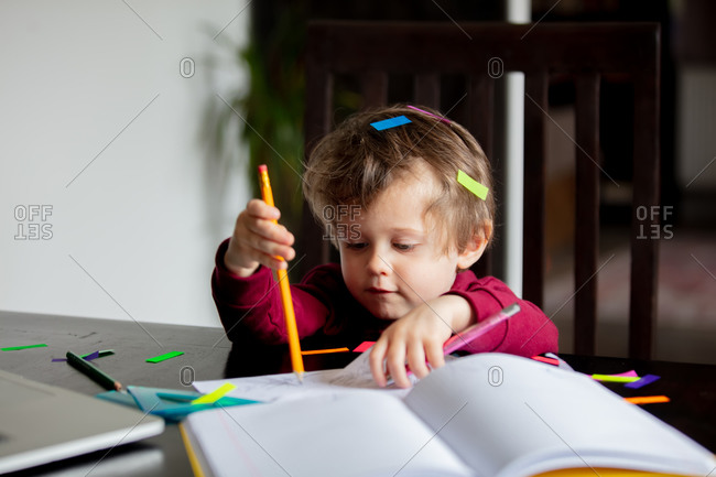 Toddler boy is playing with working documents and other parents tools