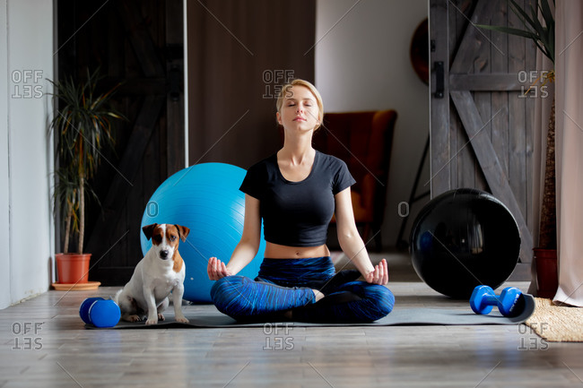 Woman doing yoga at home, with a dog sitting next to her