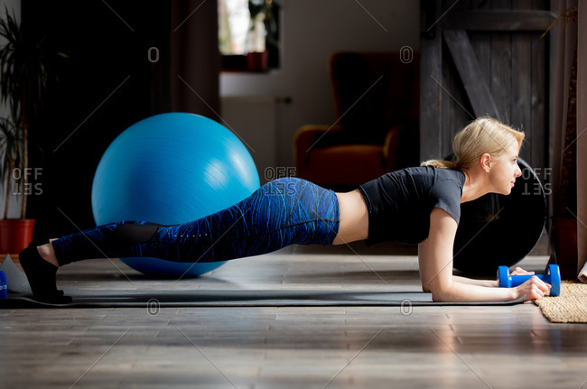 Young woman doing plank at home