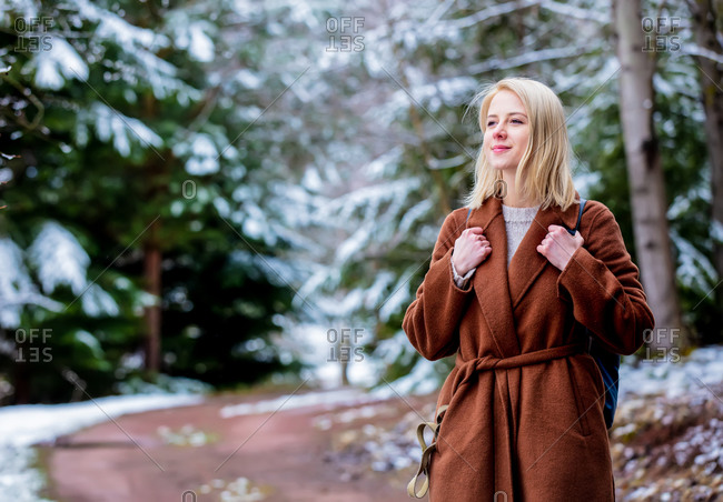 Style blonde woman in coat in snow forest