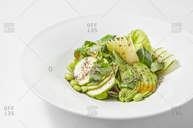 Freshly cooked homemade vegan salad from natural organic vegetables and fruits on a ceramic plate on a light grey background, copy space.