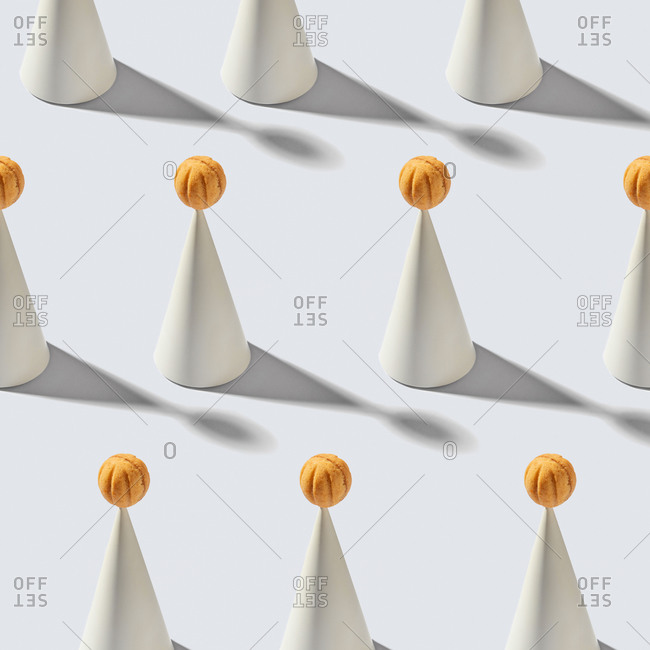 Composition of plaster cones with shadows and freshly baked cookies in the shape of walnuts on a light gray background with hard shadows.