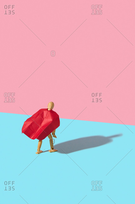 Movable human miniature model in red cape as a superhero or superman is standing on a duotone background with hard shadows.
