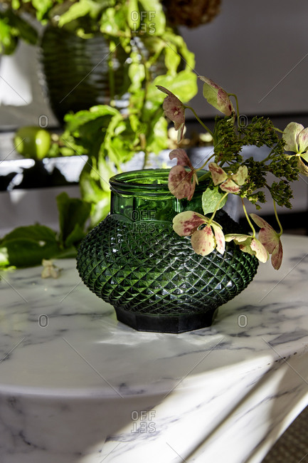 A close up of a small green glass vase on a marble table with flowers,