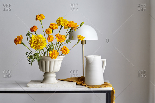 Still-life arrangement of yellow and orange carnation and a white ceramic jug and a white lamp,