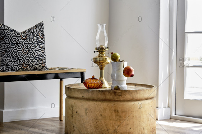 Tabletop still life of a vintage oil lamp, a marble vase with a pomegranate branch and a burnt orange glass bowl with a  wooden bench and a decorative scatter cushion,