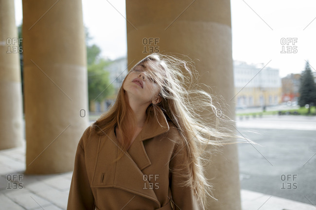 Young woman with windblown hair by columns