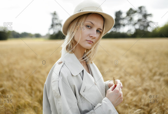 Young woman with fedora in wheat field