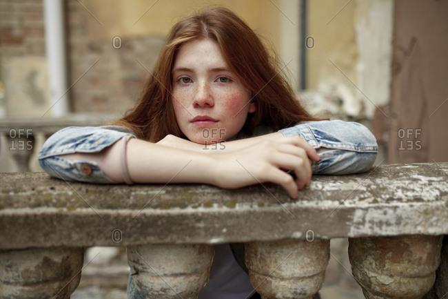 Teenage girl leaning on stone banister