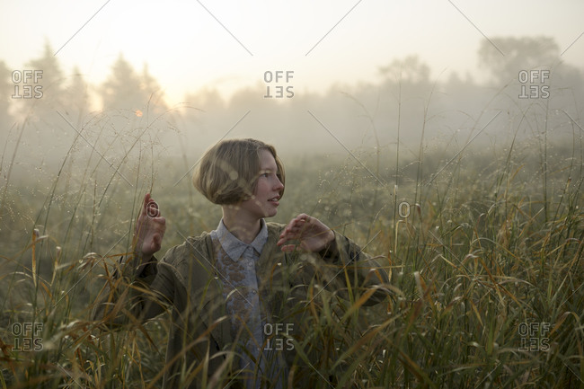 Young woman in field of long grass