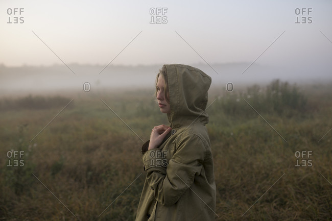 Young woman in field at sunset