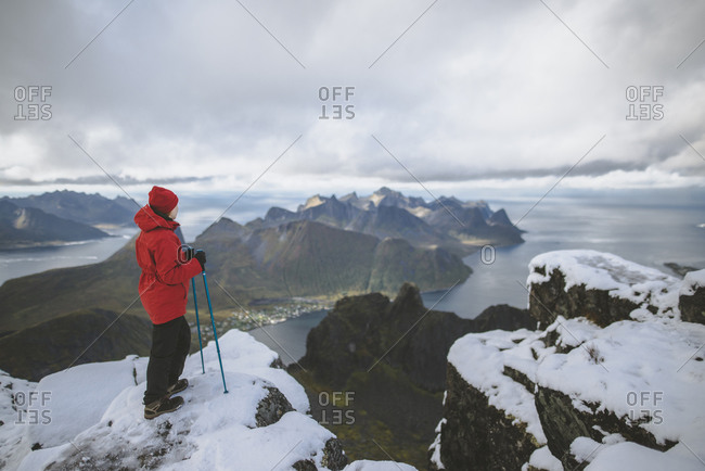 Young woman in red jacket with hiking poles on snowy mountain