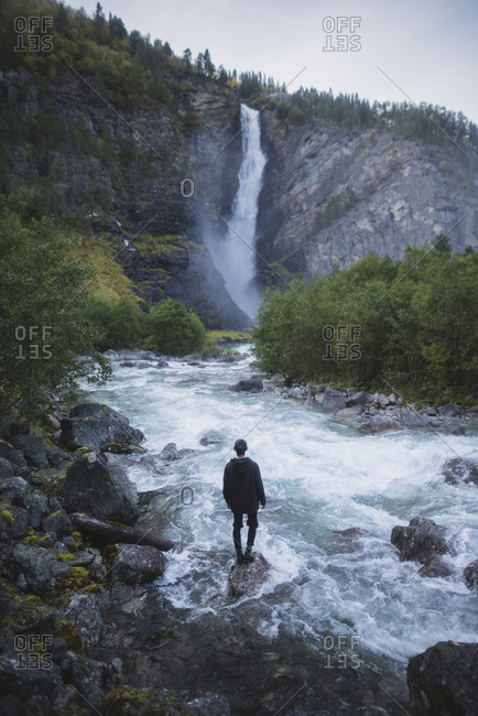 Young man standing by waterfall