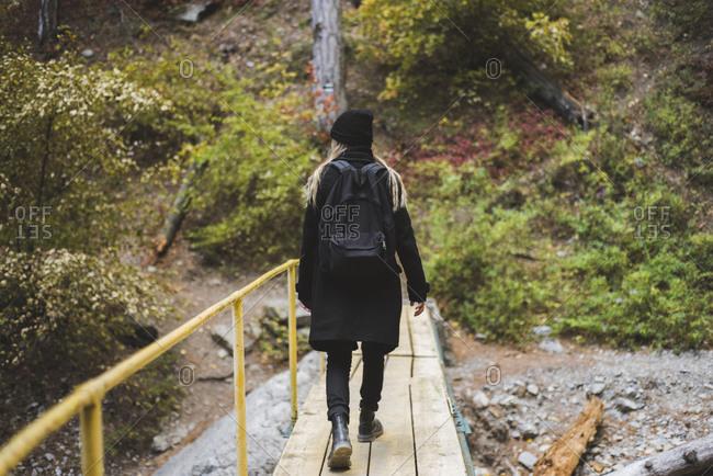Young woman walking across bridge in forest