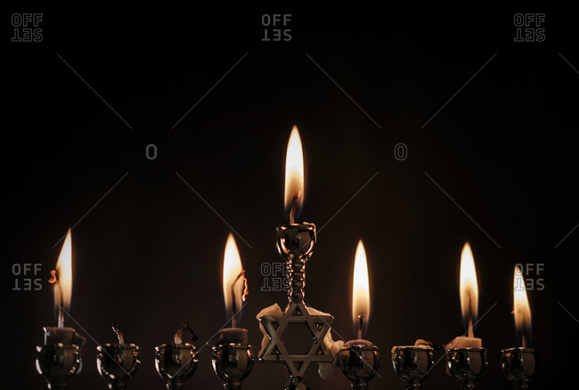 Lit candles in silver menorah