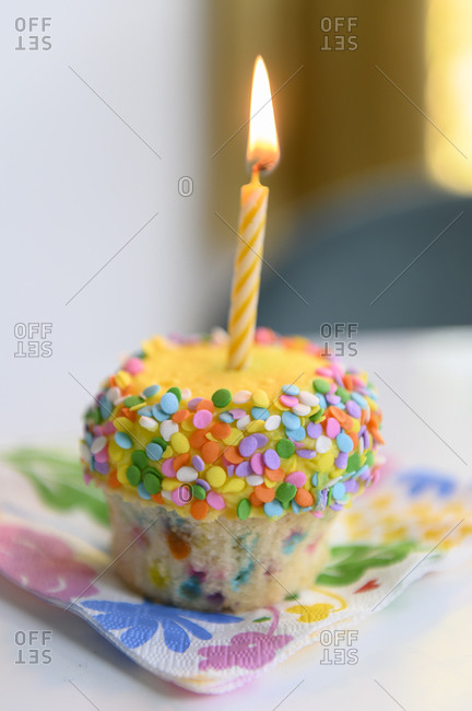 Vanilla and sprinkle cupcake with lit birthday candle