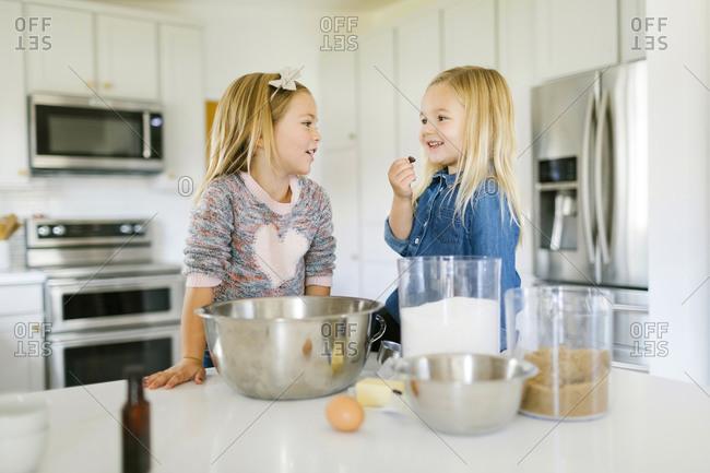 Smiling girls baking cookies at home