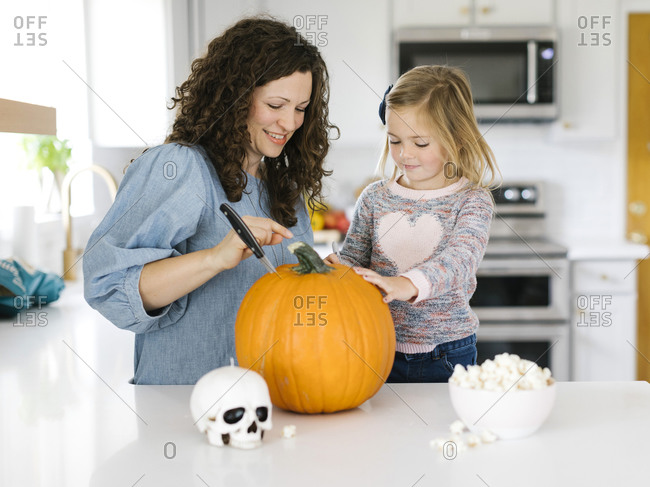 Mother and daughter carving pumpkin for Halloween