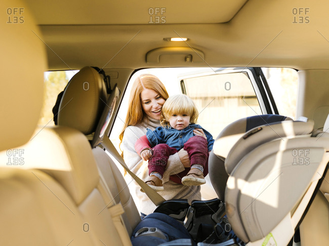 Smiling woman carrying son into car seat