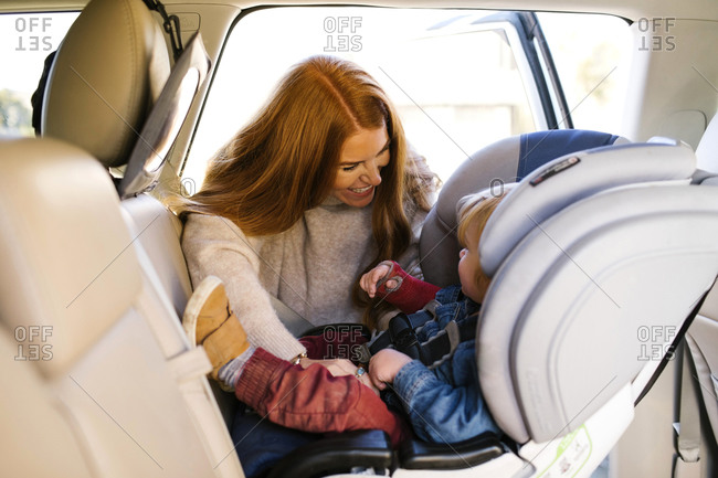 Woman smiling at son sitting in car set