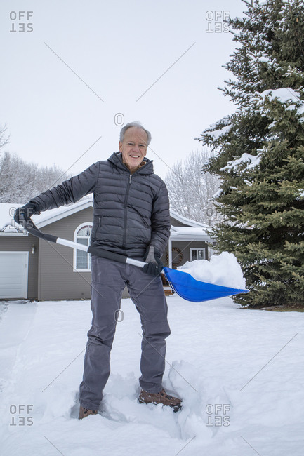 Senior man shoveling snow in front yard