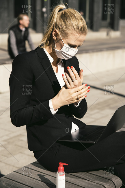 Businesswoman working with laptop waring face mask and hand sanitizer