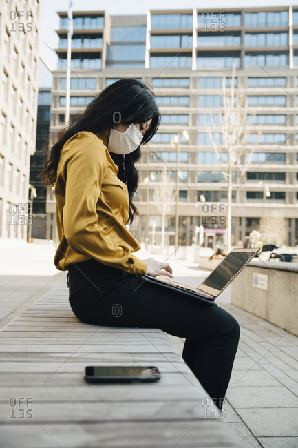 Profile of woman with face mask sitting outside working