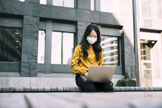 Businesswoman with face mask working using laptop