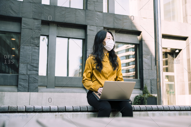 Businesswoman with laptop working outside wearing face mask