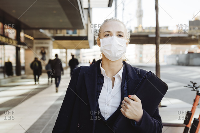 Businesswoman walking in street wearing face mask
