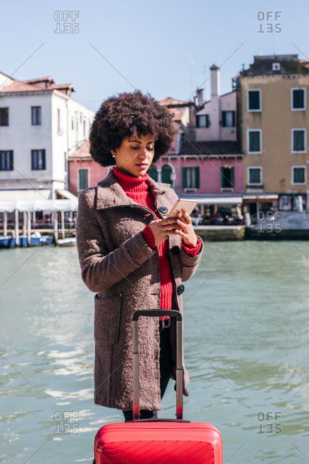 Young tourist woman checking smart mobile phone
