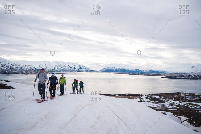 A group backcountry skiing in Iceland with the ocean in the background